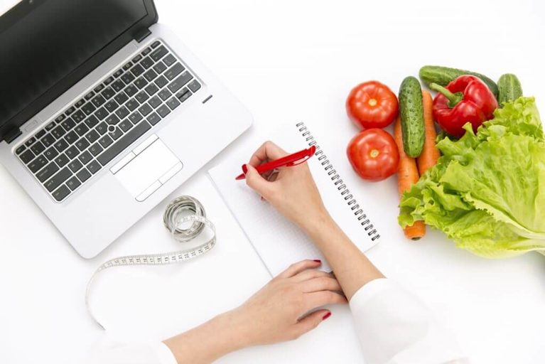 Person Writing Notes with a Laptop, Vegetables, and Measuring Tape