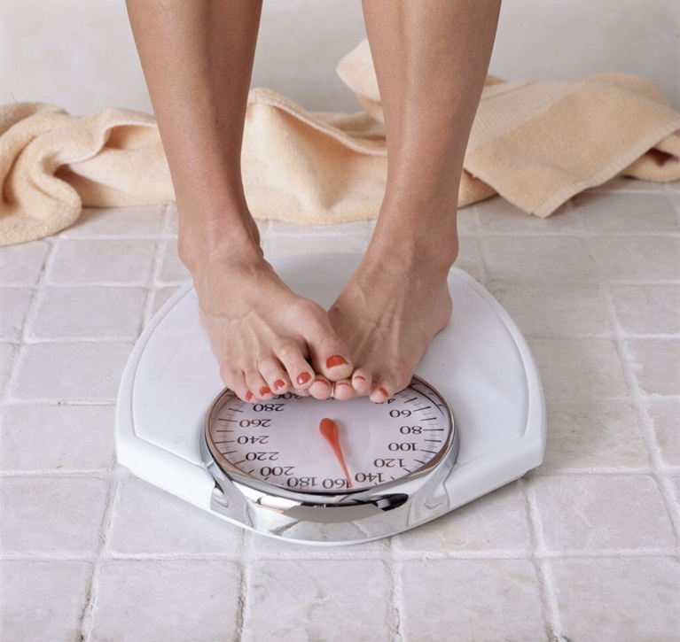 Person's Feet Standing on a Weighing Scale