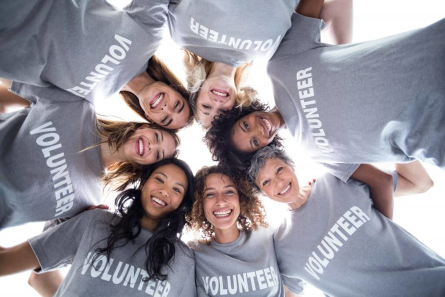 Female Volunteers Banning Together, Smiling