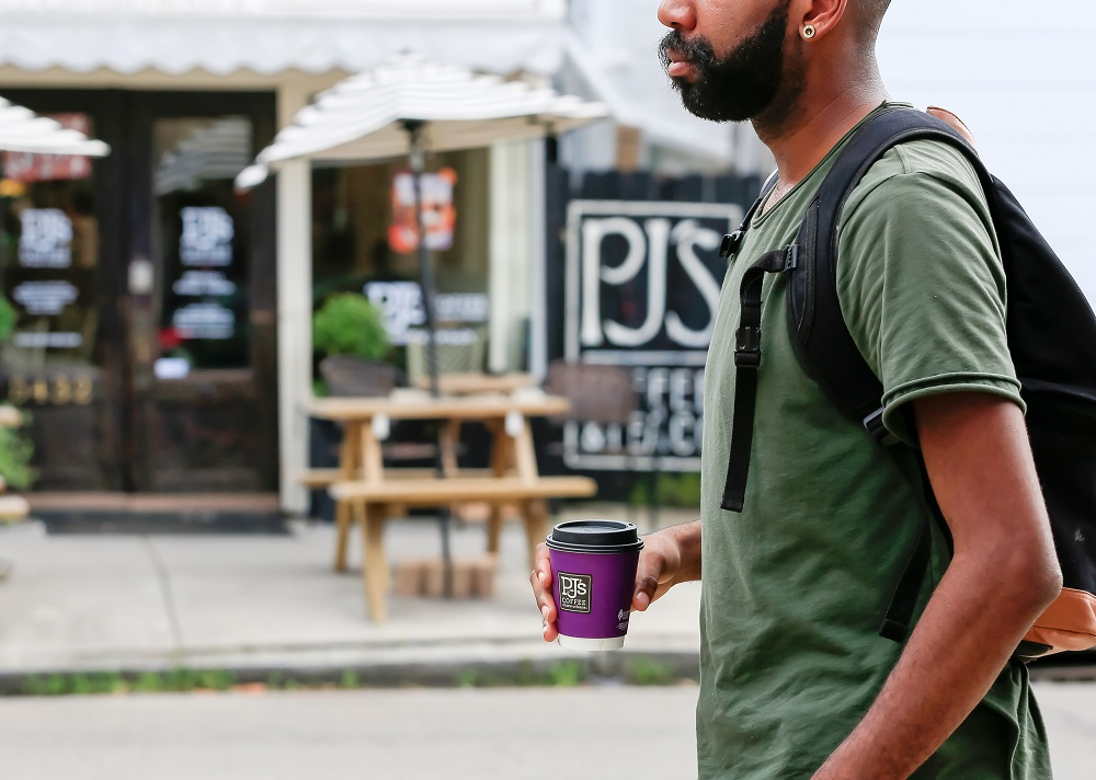 person walking with PJ's Coffee cup